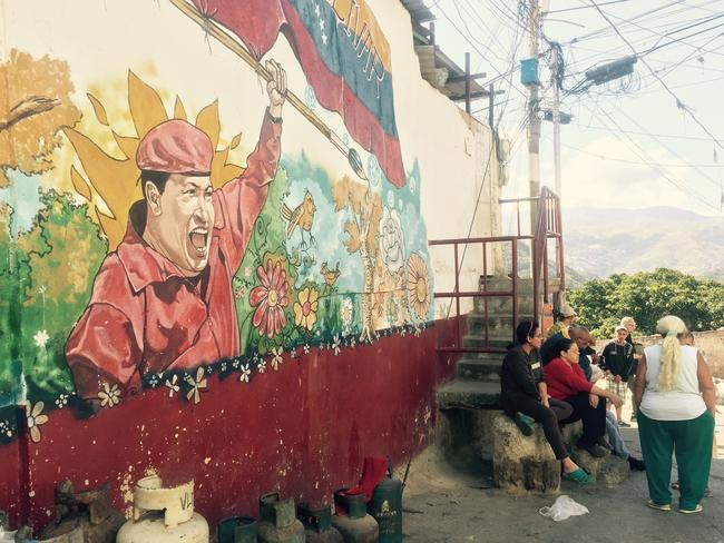 Locals gather around a mural of former president and leader of the socialist revolution, Hugo Chavez. Picture: Courtesy of the ABC