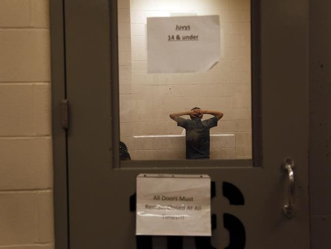 Detained ... an immigrant who was detained at the border is held inside the McAllen Border Patrol Station in McAllen, Texas in an area for juveniles 14 and under. Picture: AP