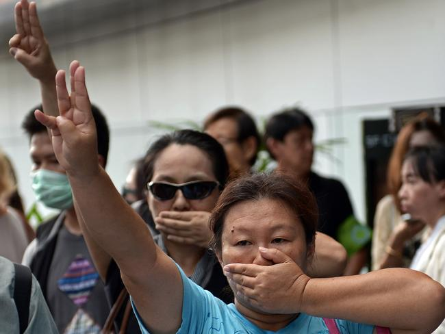 Silent protest ... anti-coup protesters flashing a  <i>Hunger Games</i>-style three-finger salute during a gathering at a shopping mall which was broken up by security forces in downtown Bangkok. Picture: AFP