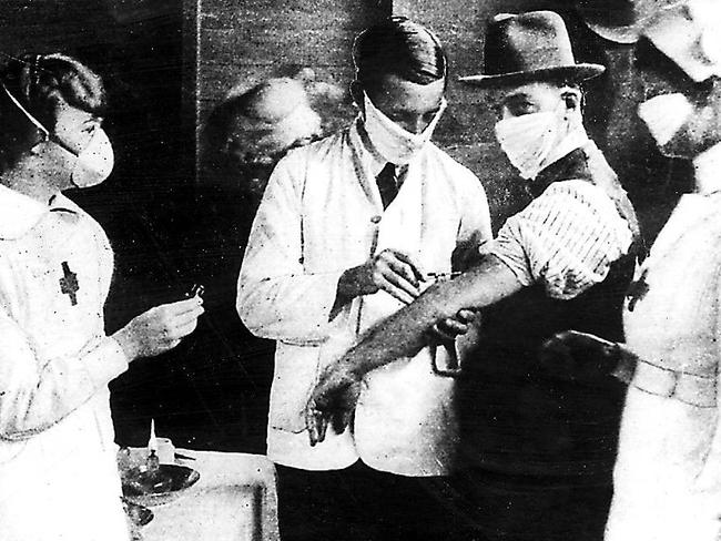 Nurses and doctors wearing protective masks vaccinate patients from Spanish influenza in 1919. The strain killed millions.