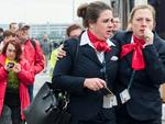 Airline stewards walk away from Brussels airport after explosions rocked the facility in Brussels, Belgium Tuesday March 22, 2016. Picture: AP Photo/Geert Vanden Wijngaert