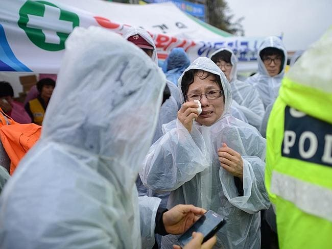 Hope fading. A relative waits for news in a makeshift tent on the dock in Jindo, coast guard officials admitted there was almost no chance of finding any of the missing hundreds alive. Picture: AFP