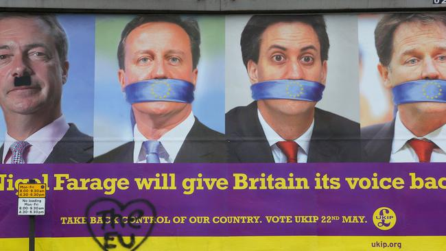 Voting ... a defaced UKIP poster shows the faces of Nigel Farage, David Cameron, Ed Miliband and Nick Clegg in Sheffield, England. Picture: Getty Images