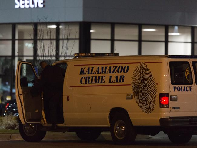 An officer with the Kalamazoo Crime Lab leaves the scene of the random shooting on Sunday. Picture: Bryan Bennett/Kalamazoo Gazette-MLive Media Group via AP