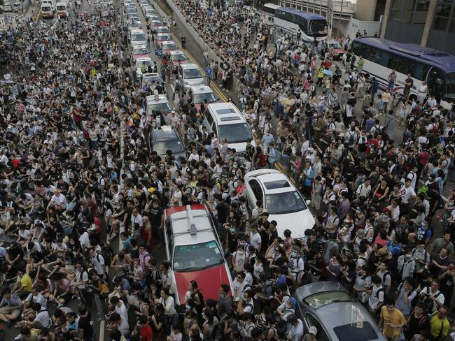 Thousands block a main road after challenging Beijing on voting reforms. Pic: AP.