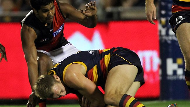Adelaide's Brent Reilly crashes into the legs of Alwyn Davey, giving away a free kick. Picture: Simon Cross