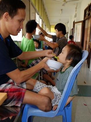 Truong Minh Hiep, aged 16, born with physical deformities feeds breakfast to Tran Thi Ngoc Nhu, aged 8, with Down 's syndrome. Photo: Ash Anand / NEWSMODO