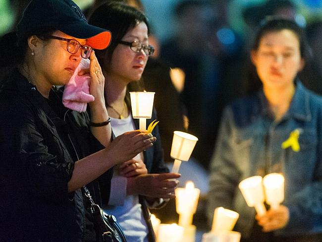 Grief ... people hold candles at a vigil for students among the missing passengers of a South Korean capsized ferry. Picture: AFP