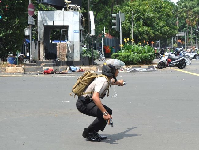 A police officer ... holds his pistol during a gunbattle with attackers near the site of an explosion. Picture: AP