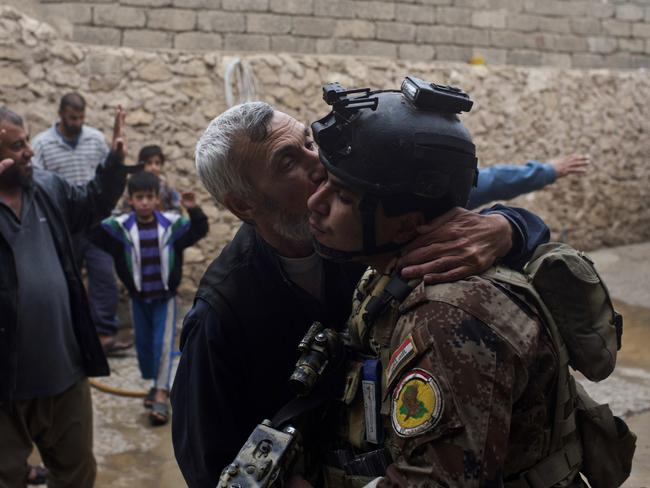 A man kisses an Iraqi special forces soldier after his house was searched, in Gogjali, an eastern district of Mosul, Iraq. Picture: Marko Drobnjakovic.