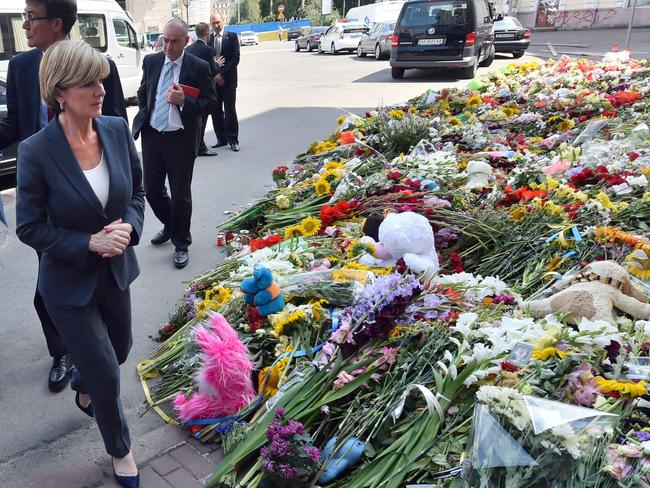 Foreign Minister Julie Bishop walks past flowers laid in memory of the victims of downed Malaysia Airlines flight MH17 in front of the Netherlands' embassy in Kiev. Picture: AFP Photo/Sergei Supinsky