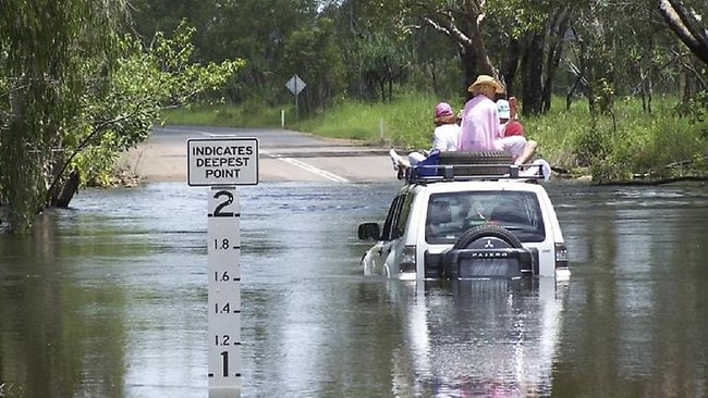Tourists atop their hire vehicle after becoming stranded in Magela Creek in 2011. They were rescued by police. Picture: NT POLICE
