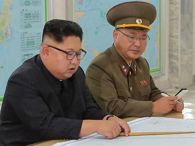"""This picture taken on August 14, 2017 and released from North Korea's official Korean Central News Agency (KCNA) on August 15, 2017 shows North Korean leader Kim Jong-Un (C) inspecting the Command of the Strategic Force of the Korean People's Army (KPA) at an undisclosed location. North Korean leader Kim Jong-Un said on August 15 he would hold off on a planned missile strike near Guam, but warned the highly provocative move would go ahead in the event of further """"reckless actions"""" by Washington. / AFP PHOTO / KCNA VIA KNS / STR / South Korea OUT / REPUBLIC OF KOREA OUT   ---EDITORS NOTE--- RESTRICTED TO EDITORIAL USE - MANDATORY CREDIT """"AFP PHOTO/KCNA VIA KNS"""" - NO MARKETING NO ADVERTISING CAMPAIGNS - DISTRIBUTED AS A SERVICE TO CLIENTS THIS PICTURE WAS MADE AVAILABLE BY A THIRD PARTY. AFP CAN NOT INDEPENDENTLY VERIFY THE AUTHENTICITY, LOCATION, DATE AND CONTENT OF THIS IMAGE. THIS PHOTO IS DISTRIBUTED EXACTLY AS RECEIVED BY AFP.  /"""