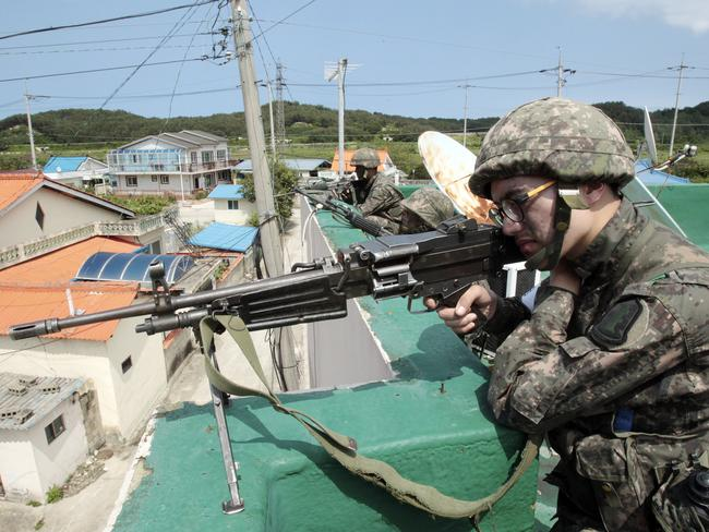 Runaway soldier...South Korean army soldiers aim their machine guns as they search for a South Korean soldier who is on the run after shooting five comrades on the border. Picture: