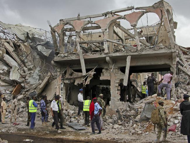 Somali security forces and others gather and search for bodies near destroyed buildings at the scene of Saturday's blast. Picture: AFP