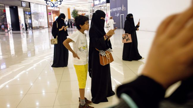 Women use their smartphones while visiting the Al Yasmin mall in Jeddah, Saudi Arabia. Photo: Bloomberg via Getty