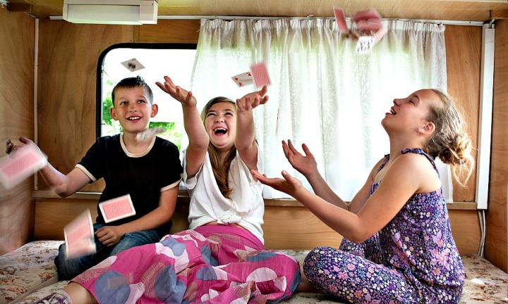 children in a trailer throwing cards in the air