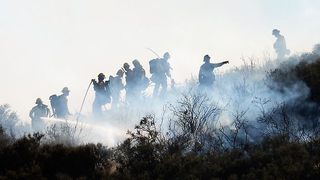 Fire firghters put out hot spots on a hillsdie behind homes by the out of control wildfire in Newbury Park, California.