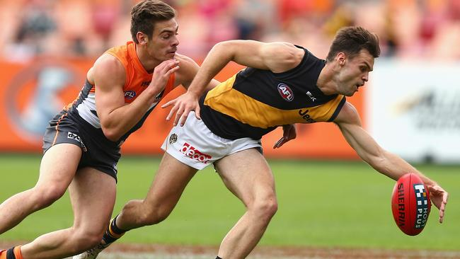 Young Tiger Ben Lennon leads Stephen Coniglio to the footy.
