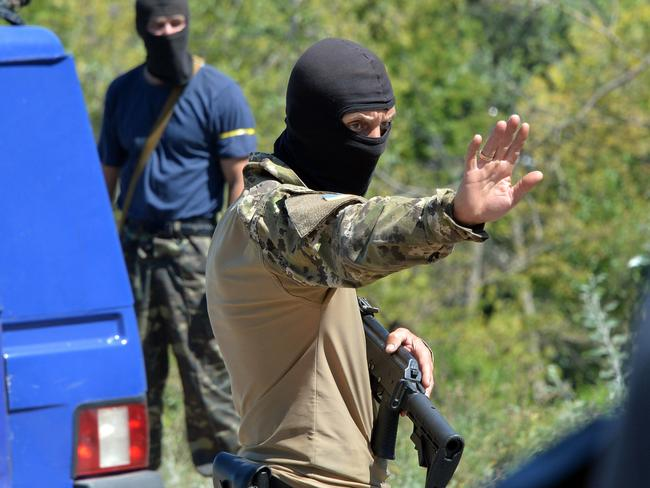 Masked gunmen stop vehicles near the site where Malaysian airliner MH17 crashed. AFP/Genya Savilov