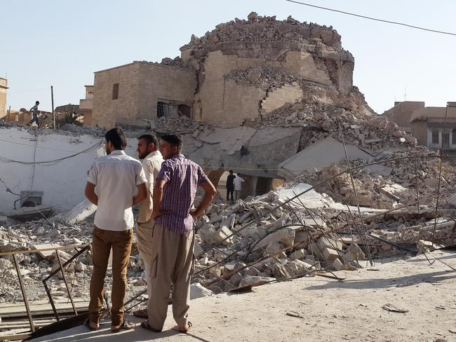 Cultural wasteland ... Residents inspect the destroyed Mosque of The Prophet Jirjis (Jonah) in central Mosul.