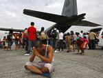 A survivor from Tacloban, which was devastated by Typhoon Haiyan, gestures while sitting on the ground after disembarking a Philippine Air Force C-130 aircraft at the Villamor Airbase in Manila, Philippines. Picture: AP