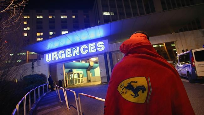 A Ferrari fan waits in front of the emergency department of the Grenoble hospital where Michael Schumacher is being treated for a severe head injury.