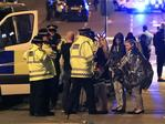 Emergency services personnel speak to people outside Manchester Arena after reports of an explosion at the venue during an Ariana Grande concert in Manchester. Picture: AP