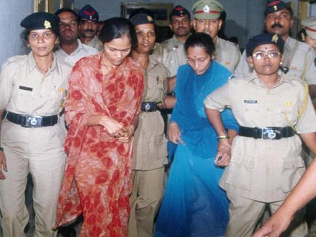 Officers escort Seema Mohan Gavit (red sari) and Renuka Shinde to an appeal hearing. Picture: Hindustan Times