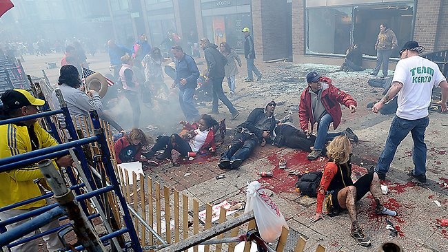 Injured peoples lie on the footpath after a bomb exploded near the Boston Marathon finish line. Picture: AP Photo/MetroWest Daily News, Ken McGagh