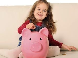 Happy little girl putting coin into huge piggy bank on sofa