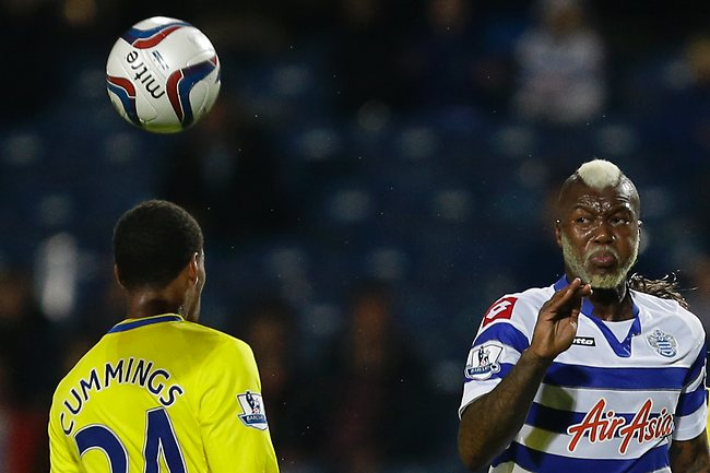 Queens Park Rangers' Djibril Cisse, right gets the ball past Reading's Shaun Cummings during their English League Cup match at Loftus Road. Pictrure: Alastair Grant