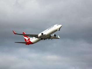 Adelaide, Australia - April 26, 2015: On a cloudy overcast day, a Qantas 737-838 aeroplane lifts off the runway and becomes airborne. Its landing wheels are almost retracted for the flight.