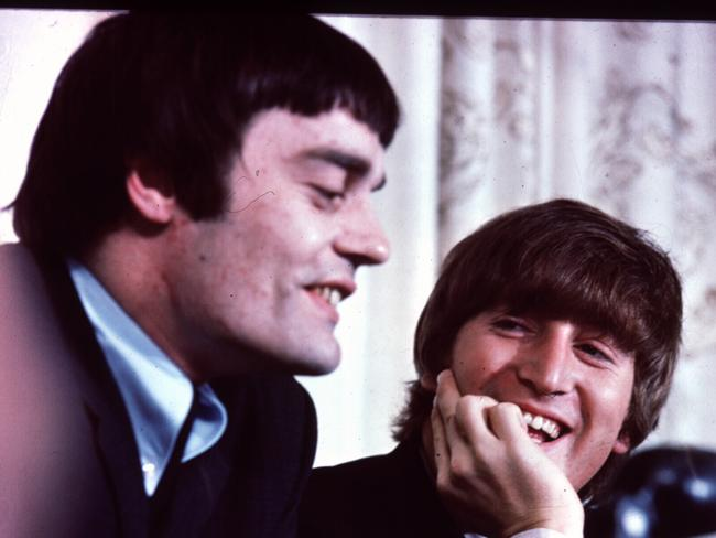 John Lennon smiles as Jimmy Nicol speaks to the media.