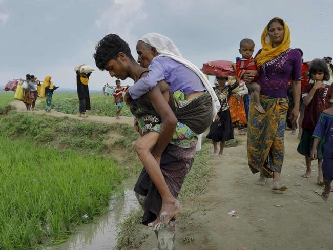 A young man helps an old woman flee Myanmar's Rakhine state for Bangladesh. Picture: K.M. Asad