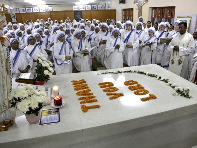 Celebration ... Archbishop of Calcutta Thomas D'Souza (right) and nuns of the Missionaries of Charity hold a special Mass at Mother Teresa's tomb in India to celebrate her canonisation. Picture: AP Photo/ Bikas Das