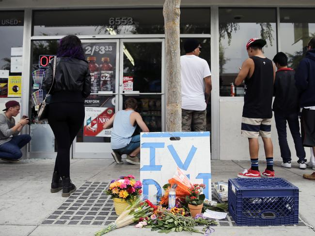 Flowers are left in front of IV Deli Mart, where part of the mass shooting took place.
