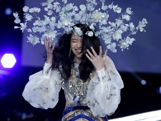 Model Ming Xi falls to her knees during the Victoria's Secret fashion show at the Mercedes-Benz Arena in Shanghai, China, Monday, Nov. 20, 2017. (AP Photo/Andy Wong)