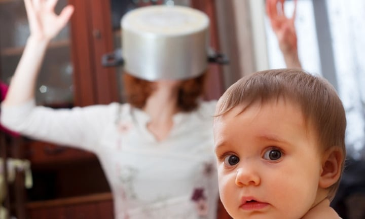 Portrait of scared baby against crazy mother with pan on head