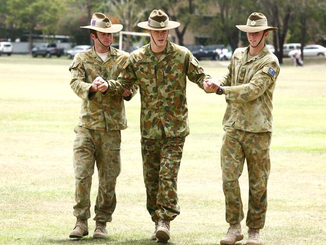 Curtis is supported by two mates as he joins the welcome home parade march at the Gallipoli Barracks Enoggera. Picture: Tim Marsden