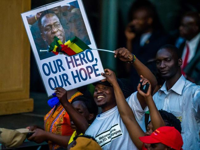 Supporters hold banner, wave Zimbabwean national flag and cheer as they gather to welcome Zimbabwe's incoming President Emmerson Mnangagwa. Picture: AFP