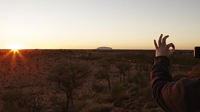 A tourist takes a photo of sunrise and Uluru, from the Olgas viewing platform. Picture: Lisa Perkovic