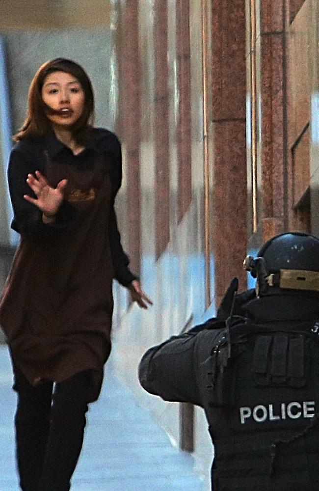 A terrified Ms Chen flees from the Lindt cafe s towards an armed tactical response police officer at Martin Place. Picture: Rob Griffith