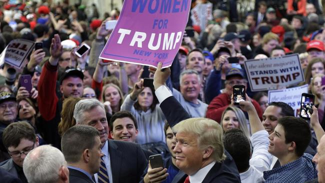 Donald Trump holds up a sign handed to him by a supporter after speaking at a campaign rally, Wednesday, April 6, 2016, in Bethpage, New York. Picture: Julie Jacobson/AP