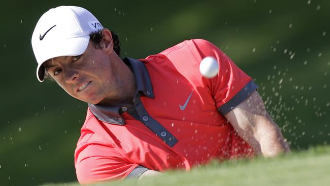 Rory McIlroy hits out of a bunker on the 18th.