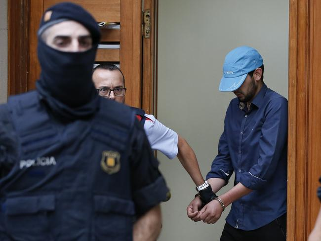 Catalan autonomous police officers detain a cuffed suspect in Ripoll during a search linked to the deadly terror attacks in Barcelona and the seaside resort of Cambrils. Picture: AFP