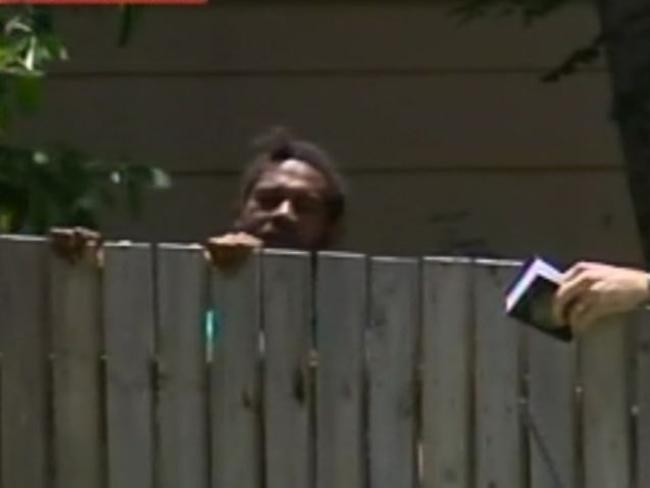 A man weeps behind a fence near the Murray St home where eight siblings have been found dead. Picture: Sky News