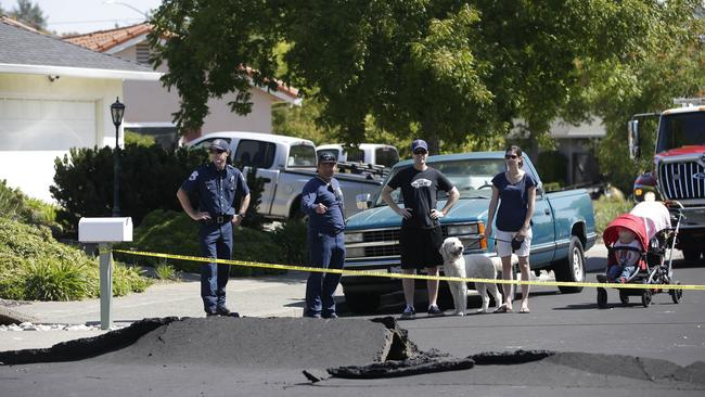 Traffic chaos ... Yellow caution tape keeps traffic from passing, after a street buckled during an early morning earthquake Sunday, Aug. 24, 2014, in Napa, Calif. Picture: AP
