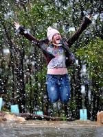 "Georgia Nielsen from Lenswood jumps through snow flakes for the first time at Mt Lofty, saying: "" It tasted delicious like a flavourless slushy"" . Picture: Mark Brake"