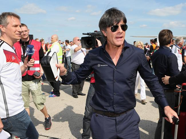 German coach Joachim Loew is approached by the media after arriving at Berlin airport.